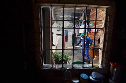 A Health Secretary employee fumigates against Aedes Aegypti mosquito Thursday inside a house in Cali, Colombia.