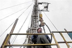 A Range Resources worker stands near a rig that's drilling into the Marcellus Shale near Washington, Pa., in 2011.