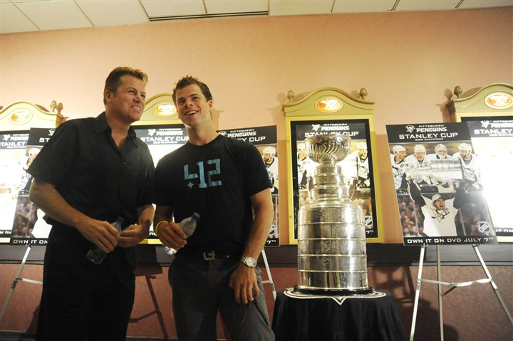 8c100kcx Phil Bourque stands with former Penguin Tyler Kennedy next to the Stanley Cup in 2009.