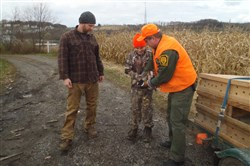 Eric Fabian of Richland looks on as his son Jesse helps to stock ring-neck pheasants on a Hunter Access property in Allegheny County.