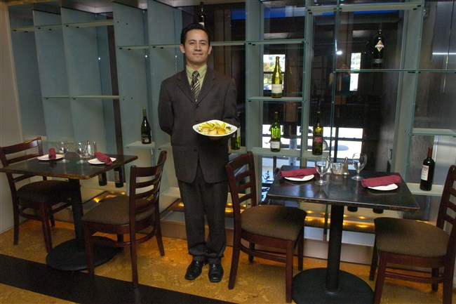 In this 2005 photo, co-Owner Horacio Ruiz holds grilled scallops in mango sauce in the Wine Room at Ibiza on the South Side.