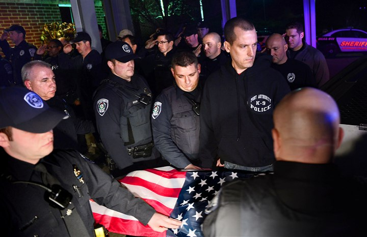 20160131JRk9officer3a-2 A Port Authority police dog who died after being stabbed during a foot pursuit Sunday in Wilkinsburg is draped in an American flag and carried out of Pittsburgh Veterinary Specialty & Emergency Center in Ohio Township.