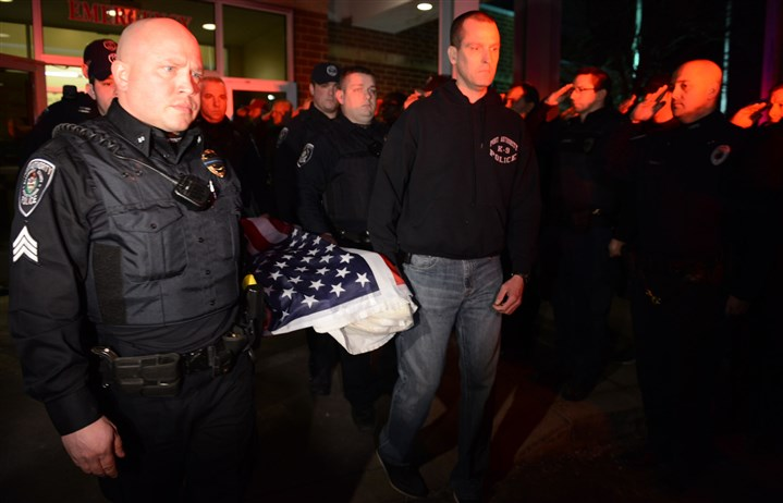 20160131JRk9officer1a The K-9 draped in an American flag is carried out of Pittsburgh Veterinary Specialty & Emergency Center by fellow Port Authority officers.