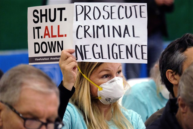 In this Jan. 16, 2016, file photo, Tera Lecuona, resident of the heavily impacted Porter Ranch area of Los Angeles, holds a protest sign during a hearing in Granada Hills over a gas leak at Southern California Gas Company's Aliso Canyon Storage Facility.