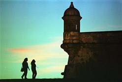 Tourists walk near the 16th century Spanish fort called El Morro in Old San Juan, Puerto Rico.