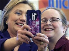 Democratic presidential candidate Hillary Clinton holds the phone to take a selfie with an employee at Market Basket Supermarket on Tuesday in Manchester, N.H.