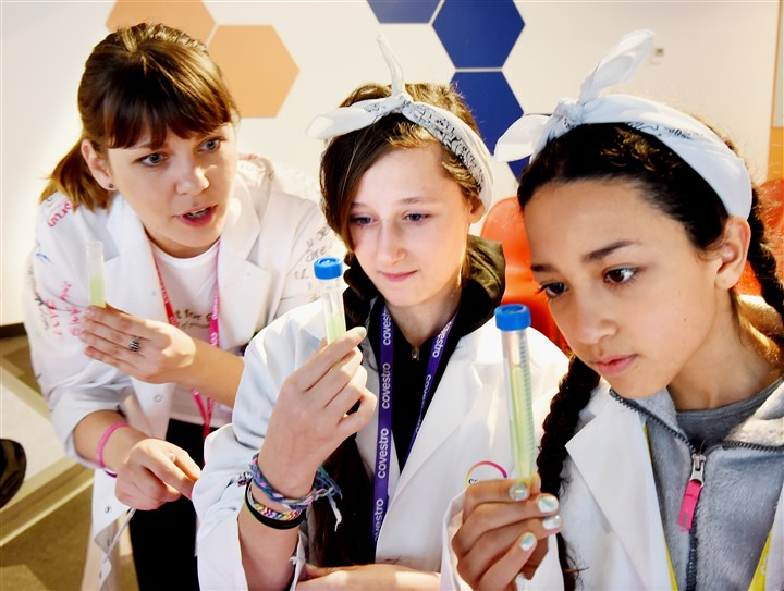 20160203radGreenlightBiz06-5 Teacher Jelena Lucin, left, tells Madison Langer and Jali Ransom, right, what to watch for as their DNA becomes visible in a sample tube Wednesday at a Covestro and greenlight for girls event to promote STEM education at Carnegie Science Center.