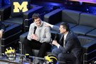 Michigan coach Jim Harbaugh, right, talks with Tom Brady at the school's signing day spectacle Wednesday in Ann Arbor, Mich.