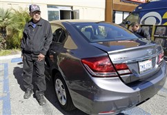 Long Hoang Ma, a California taxi driver held hostage for a week by three escaped inmates, stands next to his taxi during an interview at the offices of Vietnamese-language newspaper Nguoi Viet in Westminster, Calif., on Wednesday.
