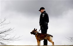 A Port Authority K-9 Officer stands with his K-9 partner during the memorial service for fellow K-9 Officer, Aren, at the Allegheny County Law Enforcement Officers Memorial on the North Shore.