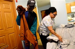 Christina West, right, helps 82-year-old Roosevelt Turner fold his clothes Thursday at his apartment in Garfield.