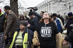 Detroit resident Elmarie Dixon, left, and Flint, Mich., resident Tammy Brewer join hands with others in prayer in front of the Rayburn House Office Building in Washington D.C.