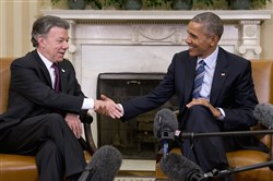 President Barack Obama shakes hands with Colombian President Juan Manuel Santos during their meeting Thursday in the Oval Office of the White House in Washington.