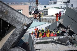 A survivor transported by rescue workers at a collapsed building on Sunday in Tainan, Taiwan. A magnitude 6.4 earthquake hit southern Taiwan early Saturday, toppling several buildings, killing at least fourteen people, and leaving over one hundred missing in Tainan.