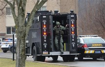 A member of the Allegheny County SWAT team disembarks a truck while responding to reports of an active shooter in an apartment building on Penn Center Boulevard in Wilkins.