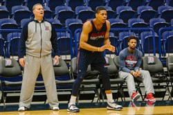 Duquesne senior guard Jeremiah Jones sits on a chair during practice at A.J. Palumbo Center at Duquesne in Uptown on Monday.   Coach Jim Ferry and player L.G Gill are also pictured.