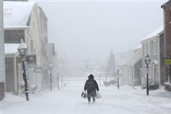 A woman walks down the street in New Bedford, Mass., on Monday.