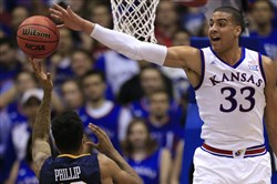 Kansas forward Landen Lucas, right, blocks a shot by West Virginia guard Tarik Phillip during the first half in Lawrence, Kan., Tuesday.