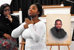 Kimara King performs a spiritual dance and reading at a memorial service Monday for her cousin, Bruce Kelley Jr., in photo at right, at Apostolic Christian Temple in Washington, Pa.