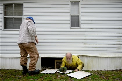 Lewis Jim Fogle crawls out from beneath the Indiana First Church of the Nazarene after volunteering to fix a leaking water pipe. He hasn't found a job since he was exonerated in September.