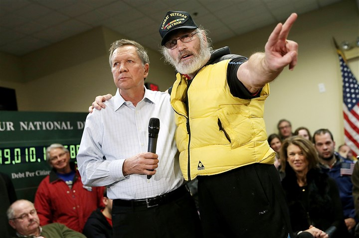 Kasich0209b-4 Vietnam veteran David AuCoin, right, puts his arm around Republican presidential candidate and Ohio Gov. John Kasich as he asks the candidate a question during a town hall Monday in Plaistow, N.H. Candidates were in a last push for votes ahead of the first-in-the-nation primary today.