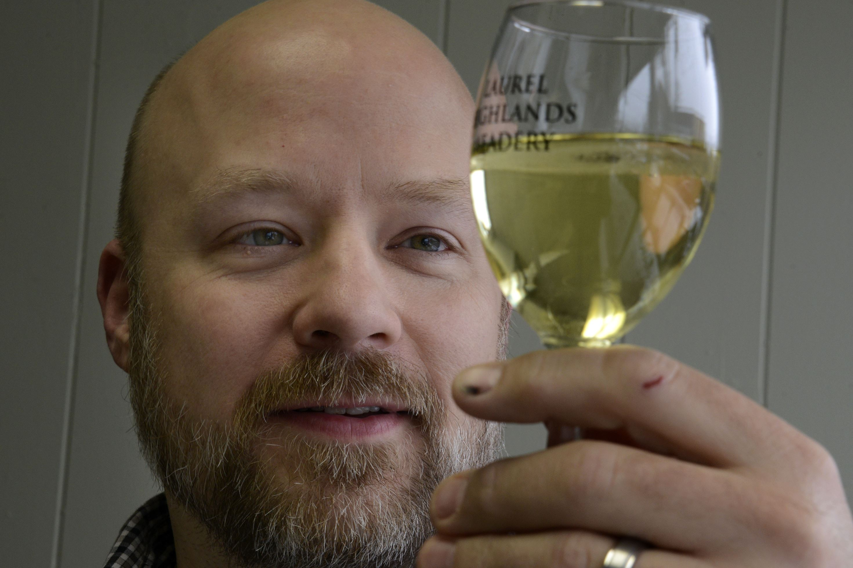 20160209dsMeaderyMag06-5 Matt Falenski looks at some of his Laurel Highlands Meadery traditional honey wine, in the light of his new shop in Irwin.