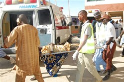 Rescue workers transport a victim of a suicide bomb attack at a refugee for treatment at a hospital, in  Maiduguri, Nigeria, Wednesday.