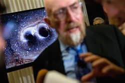 A visual of gravitational waves from converging black holes is depicted on a monitor behind LIGO co-founder Kip Thorne at the National Press Club in Washington, D.C.