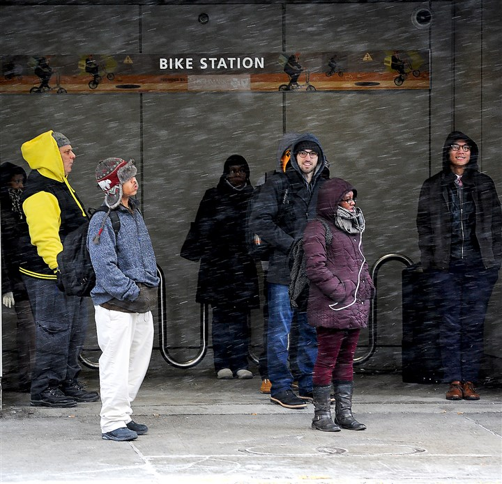 20160212rldColdWeather02-1 People are bundled up against the cold as they wait for a bus along Stanwix Street, Downtown, on Friday.
