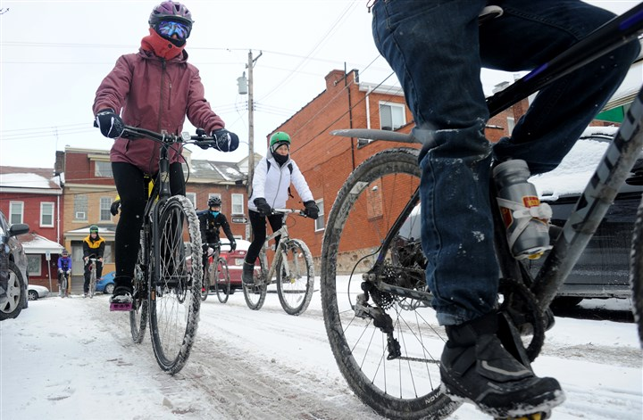 "20160213lf-Bike01-2 Cyclists ride through a snow-covered street at the 2016 ""Frigid Bitch."""
