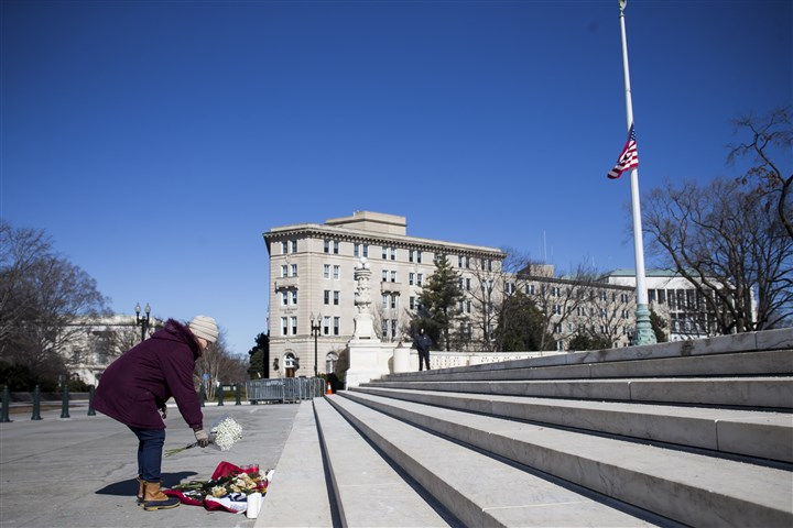 SCOTUS BATTLE 1-18 Samantha Montgomery places flowers Sunday outside the U.S. Supreme Court building in Washington, D.C., following the death of Justice Antonin Scalia.