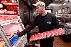 Meat cutter Ed Gordon adds a tray of 12-ounce New York strip steaks to the the meat counter at the Texas Roadhouse restaurant in Washington, Pa., where customers can choose the cut they want for their order. served at the restaurant, working in a 34-degree room most of the day optimizing each cut for customer quality. Gordon will compete with 107 Texas Roadhouse meat cutters in the company's National Meat Cutting Competition in March for a prize of $20,000. Writer: McKay. Story Slug: not available