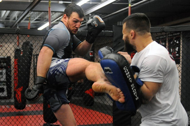20160215JHSportsMMA03-2 Mixed martial arts fighter Adam Milstead, left, delivers a kick to his trainer Mark Cherico during a workout session Feb. 15 in Collier.