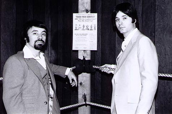 1979_mma0221_ Caliguri_Viola_01 Frank Caliguri, left, and Bill Viola Sr., right, stand in front of a poster promoting the Tough Man Contest, later called the Tough Guy Contest, the first mixed martial arts competition in the country. Mr. Caliguri and Mr. Viola were the co-founders of CV Productions, which promoted the contest. This official press photo was taken in 1979 in New Kensington.