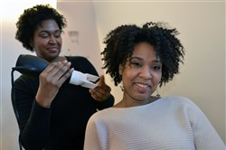 Tamiah Bridgett, founder of Diversame,  demonstrates a newly designed hair dryer on her sister, Grace Higginbotham.