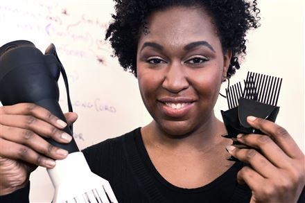 Tamiah Bridgett, founder of Diversame, holds up a prototype hair dryer.