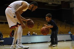 "Robert Morris forward Billy Giles dribbles with his son Cameron ""Cam"" Giles, 2, after a recent Robert Morris basketball game at Sewall Center."
