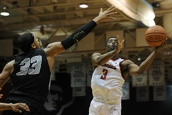 Long Island University forwawrd Jerome Frink attempts to block a shot by Robert Morris guard Kavon Stewart.