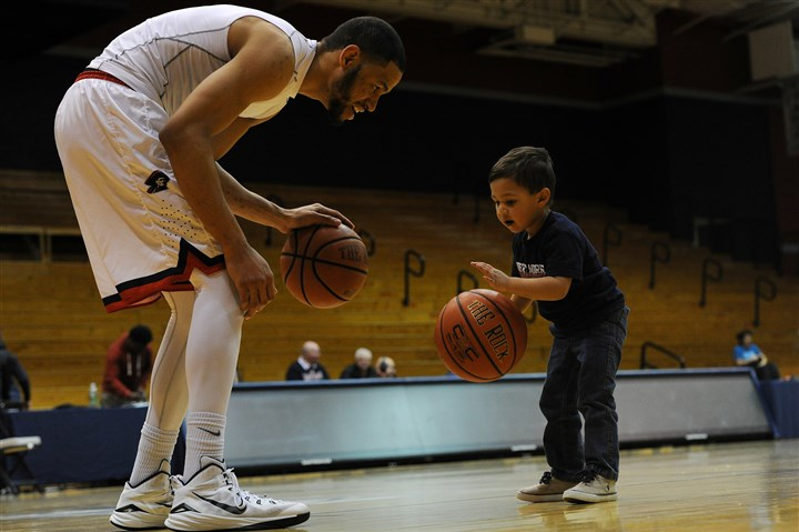 "20160219rldBillyGiles03-1 Robert Morris forward Billy Giles dribbles with his son Cameron ""Cam"" Giles, 2, after a recent Robert Morris basketball game at Sewall Center."