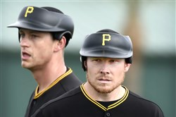 Jared Hughes, back, and Mark Melancon wear new pitcher protective caps in Bradenton.