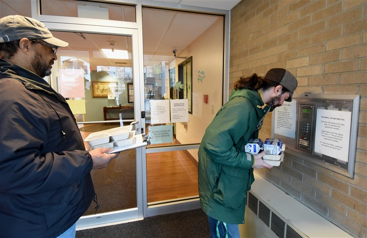 20160224radMealsOnWheelsLocal04-3 Meals on Wheels volunteers Galen Osby, right, and Bill Simmons wait for a client to open the door of a Sharpsburg apartment building to make a food delivery.