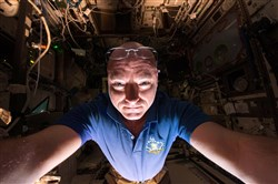 In this June 14, 2015, photo made available by NASA, astronaut Scott Kelly makes a photo of himself as he prepares a scientific experiment on the International Space Station.