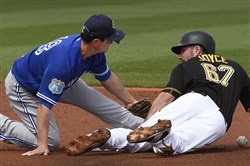 Toronto's Darwin Barney drops the ball as Pirates outfielder Matt Joyce slides into second base during a spring training game in March.