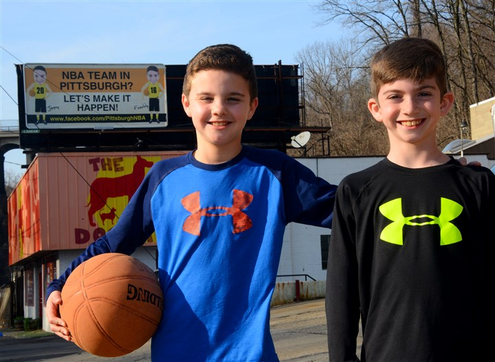 20160308lf-NBA01 Jimmy Hanna, left, 11, and his brother Freddy,10, of Fox Chapel, pose in front of the billboard they rented on Washington Boulevard to promote their cause: bringing an NBA team to Pittsburgh.