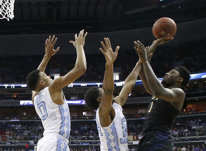 ACC Pittsburgh North Carolina Basketball-1 North Carolina guards Nate Britt, left, and Kenny Williams try to block a shot by Panthers forward Jamel Artis.