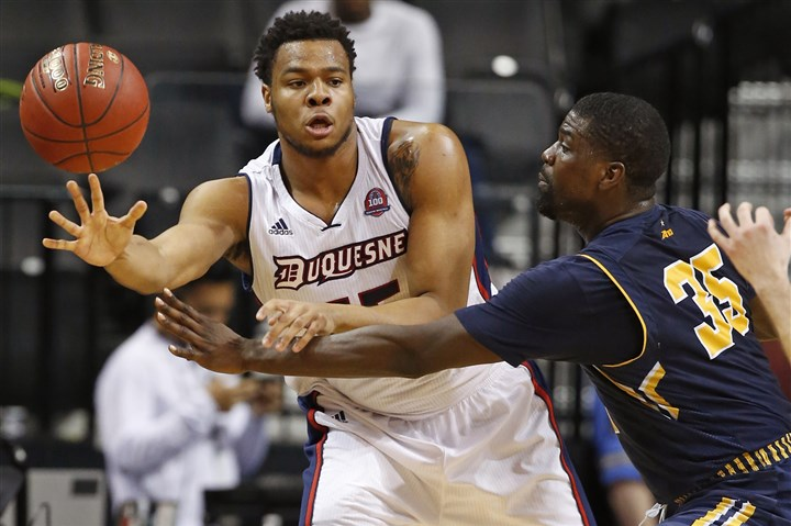 Duquesne Basketball A10 Duquesne forward Jordan Robinson passes around La Salle guard Rohan Brown during the second half of their Atlantic 10 men's basketball tournament matchup.