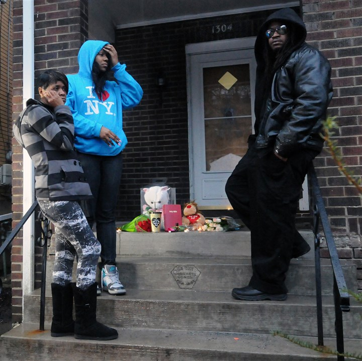 20160310JHLocalVigil01 Mourners stand in front of a make shift memorial on the steps of 1304 Franklin Ave. in Wilkinsburg where six people were shot and killed.