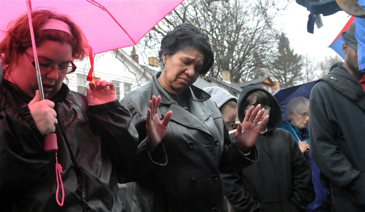 20160310JHLocalVigil07-5 Janet Harris, center, prays with other mourners at a vigil in front of 1304 Franklin Ave in Wilkinsburg.