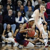 Robert Morris' Jocelynne Jones falls to the court as Connecticut's Katie Lou Samuelson defends Saturday in Storrs, Conn.