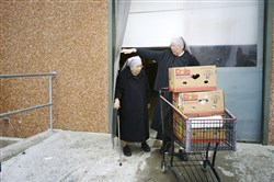 Sr. Margaret, right, helps Sr. Monique out the door as they are picking up baked goods from the Giant Eagle Market District in Robinson.